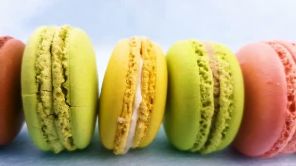 Makronky sladké barvy nebo macaron na pastelově růžové pozadí. Detailní záběr snímku