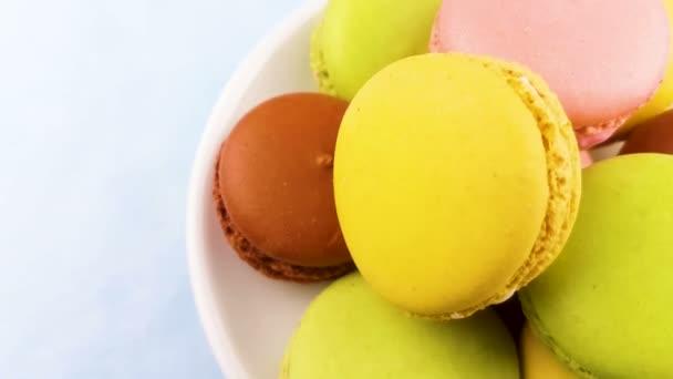 Makronky sladké barvy nebo macaron otočit na bílé plotně. Pohled shora