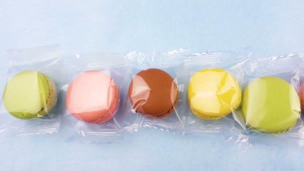 Makronky sladké barvy nebo macaron do průhledného obalu na pastelově modré pozadí. Detailní záběr