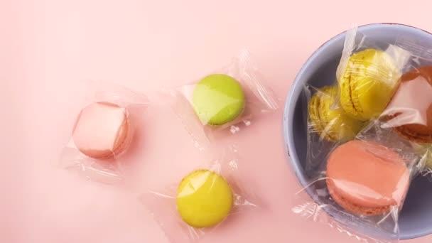 Makronky sladké barvy nebo macaron v desce na pastelové povrchu. Detailní záběr
