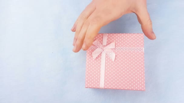Woman hand open pink box with macaroons or macaron inside on pastel blue background.