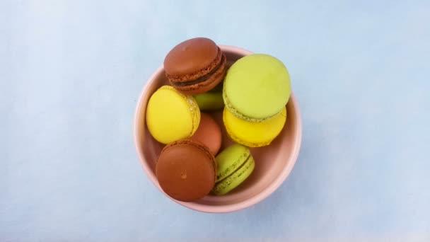 Makronky sladké barvy nebo macaron v růžové desky na pastelově modré pozadí. Detailní záběr