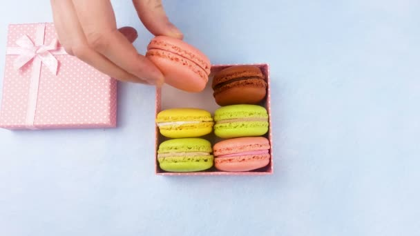Woman hand put in box sweet macaroons or macaron  on pastel blue background.