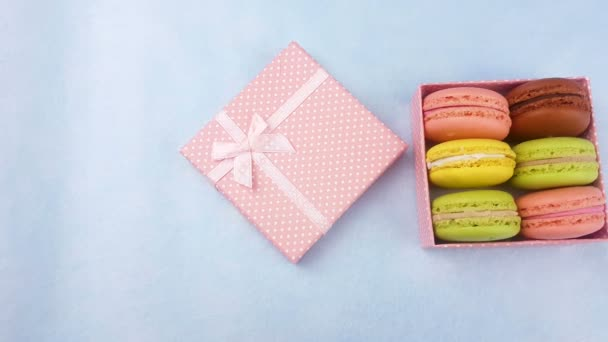 Sweet color macaroons or macaron in pastel pink gift box on blue surface.