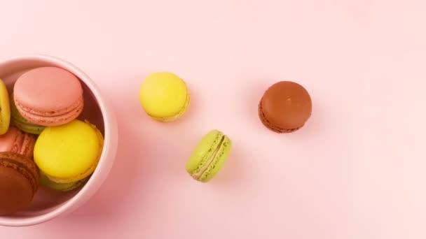 Makronky sladké barvy nebo macaron v růžové desky na pastelové povrchu. Detailní záběr