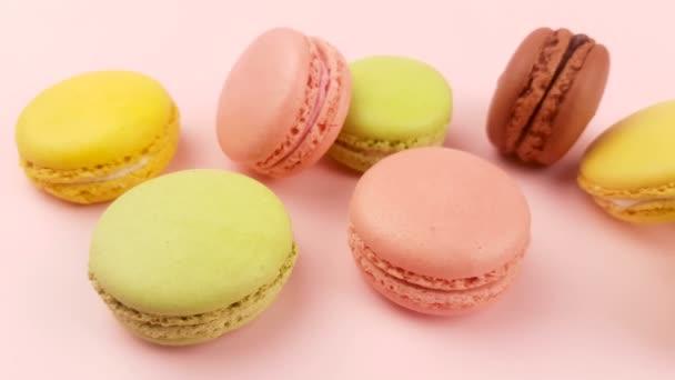 Makronky sladké barvy nebo macaron na pastelově růžové povrchu. Detailní záběr