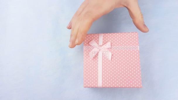 Ženská ruka otevřít Růžový box s makaróny nebo macaron uvnitř na pastelově modré pozadí