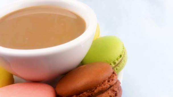 Makronky nebo macaron na pastelově růžové povrchu s kávou v bílém