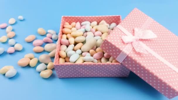 Szép pasztell színű cukorka vagy a kő, rózsaszín díszdobozban blye felületén.