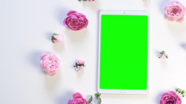 Bílá tableta se zelenou obrazovkou na stole s růžovou růžovou květinou. Letní nebo sprink pozadí záběry. Horní pohled. Záběry 4k.
