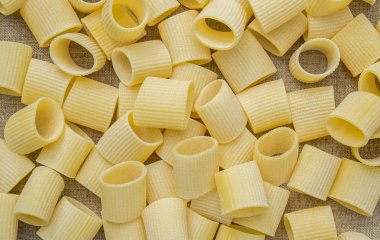 Pasta in Italian. A handful of pasta on a background of linen fabric