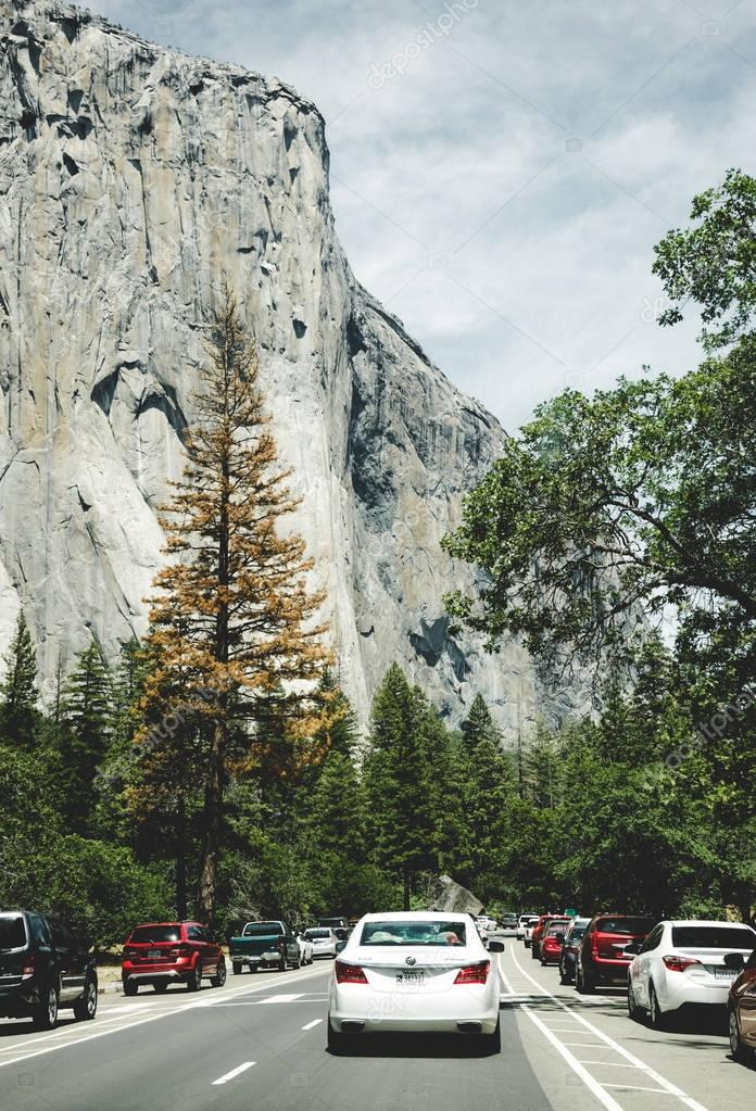 Summer car tour of the US natural parks. Tourist parking at the foot of the El Capitan cliff