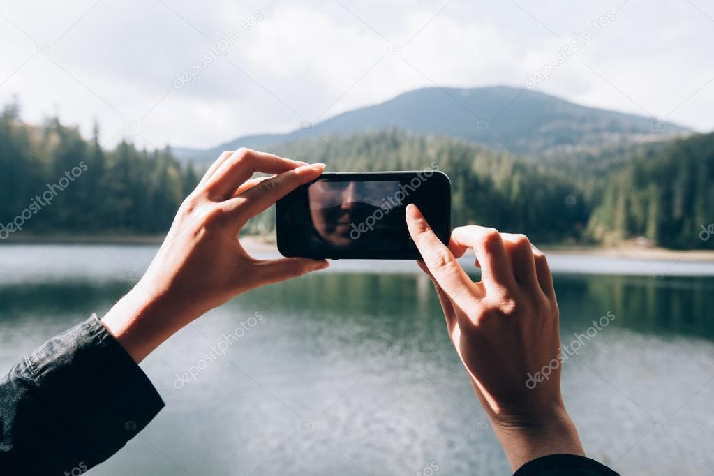 hands taking a picture of a nature with a smart phone