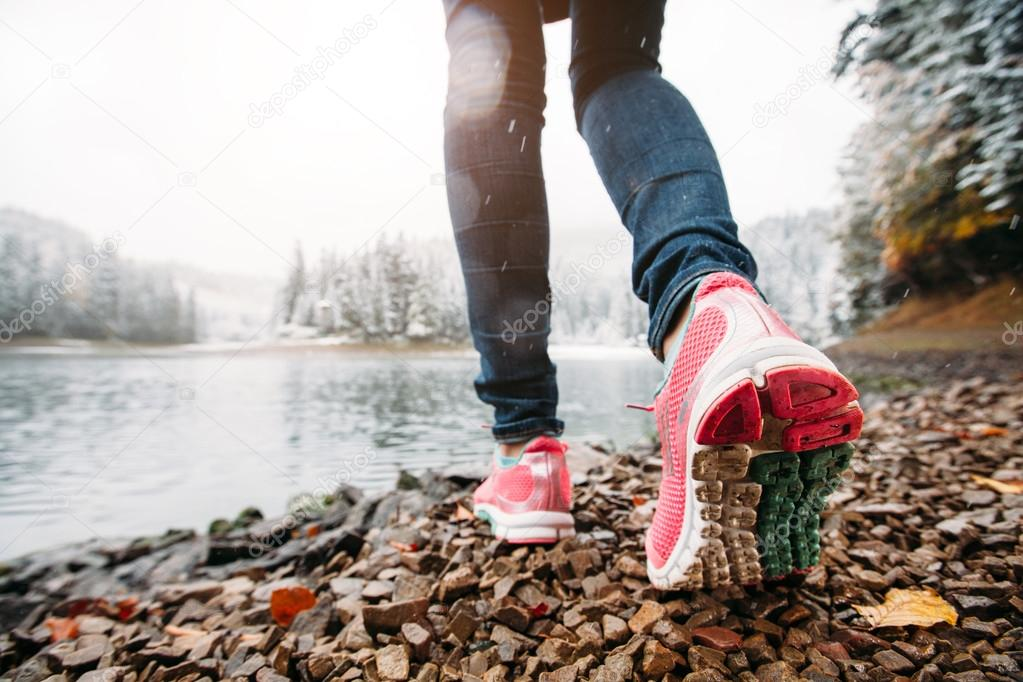 Woman hiking in the nature in winter. Low angle feet view