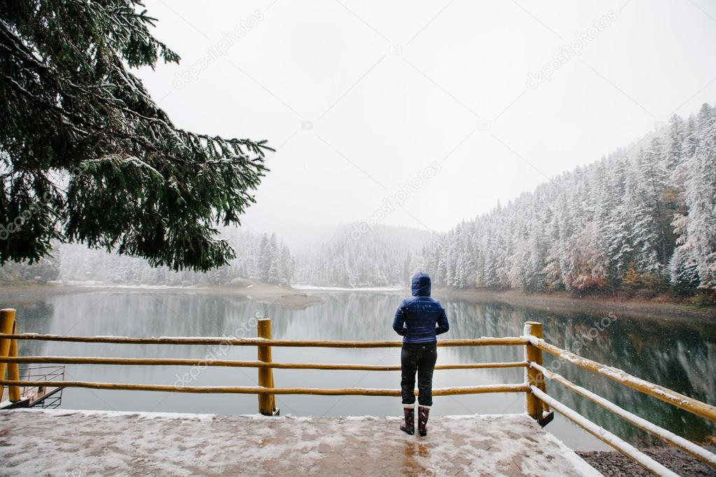 Woman looking at winter landscape in the mountains