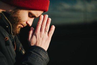 Man praying outside to God stock vector