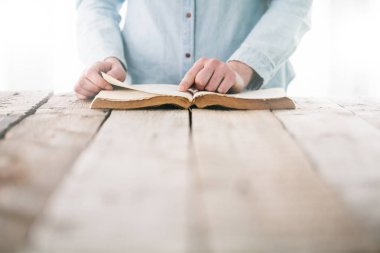 hands praying with a bible over wooden table