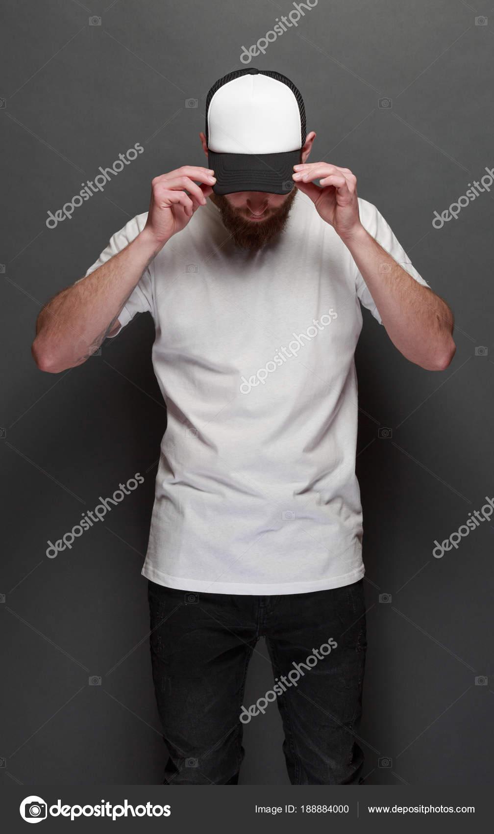 Hermoso modelo masculino hipster con barba con camiseta blanca en blanco y  una gorra de béisbol 18f4fb73315e