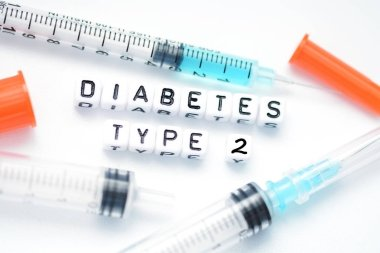 Type 2 diabetes text spelled with plastic letter beads placed next to an insulin syringe stock vector