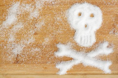 Deadly sugar addiction suggested by spilled white sugar crystals forming a skull on a wooden table