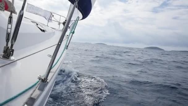 Přes palubu z bílé jachty na pozadí mořských vln v Řecku. Z obecného hlediska.