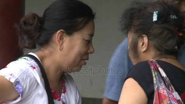 Women talk on street of city.