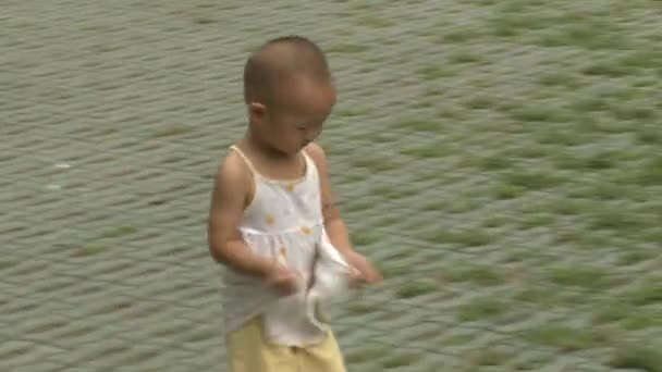Child walking on streets of city in park.