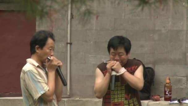 Men play on harmonica on streets of city.
