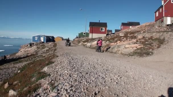 Village and people in mountains on shore of Arctic Ocean from Greenland.