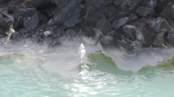 Beautiful water of geyser in mountain on shores of Arctic Ocean in Greenland.