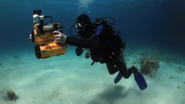 Cameraman diver swimming on sandy bottom deep underwater in Red sea.