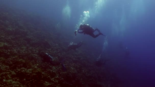Divers near wreck ship underwater on coral reef Abu Nuhas in Red sea.
