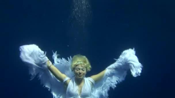 Unterwassermodel im Engelskostüm posiert im roten Meer für die Kamera.