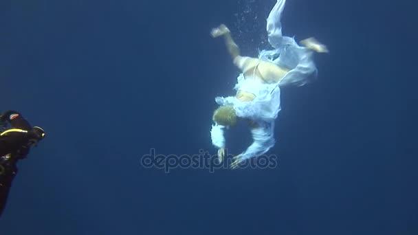 Unterwassermodell Freitaucher im Kostüm Engel schwimmt in sauberem Wasser im roten Meer.