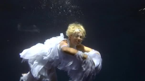Podvodní model v kostýmu anděla představuje pro fotoaparát v Rudém moři.