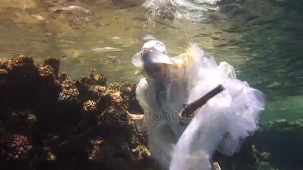 Unterwassermodell Freitaucher in Kostüm Pirat schwimmt in sauberem Wasser im roten Meer.