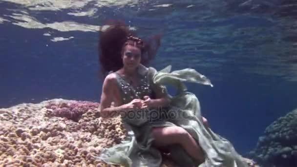 Unterwassermodell Freitaucher im Feenkostüm auf dem Hintergrund von Korallen im roten Meer.