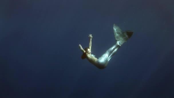 junges Mädchen Modell Unterwasser-Meerjungfrau-Kostüm auf blauem Hintergrund posiert in rotem Meer.