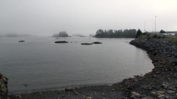 Jachty plachty na klidné vody Tichého oceánu na pozadí pobřeží silnici na Aljašce