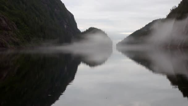 Mountains in fog on background of calm water in Pacific Ocean.
