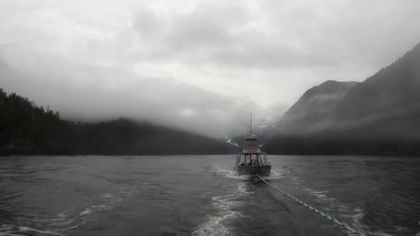 Lodní vlek v mlze na vody Tichého oceánu na pozadí hor Aljašky.