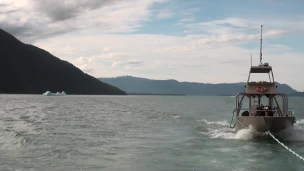 Loď v závěsu na klidné vody Tichého oceánu na pozadí ledovce a hory