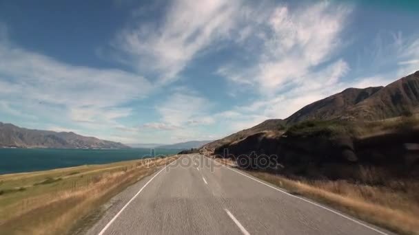 Úton a óceán partján panoráma autó ablakból, Új-Zéland.
