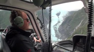 Helicopter pilot on background of mountain panorama in New Zealand.