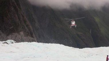 Helicopter sits down on glacier in snowy cold mountains of New Zealand.