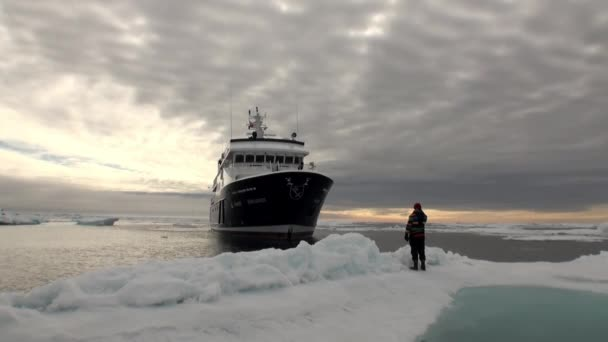 Menschen auf der Eisscholle und Schiff auf Grund des Ozeans in Arktis.
