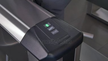Hands of people apply electronic pass to turnstile wicket checkpoint in office.