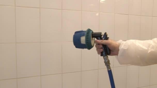 Lavaggio e pulizia di piastrelle bianche sulla parete in un