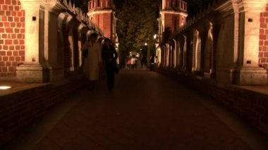 People are walking on bridge Tsaritsyno Museum in Moscow at night.