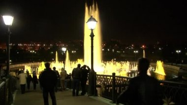 People walk at night near dancing fountains.
